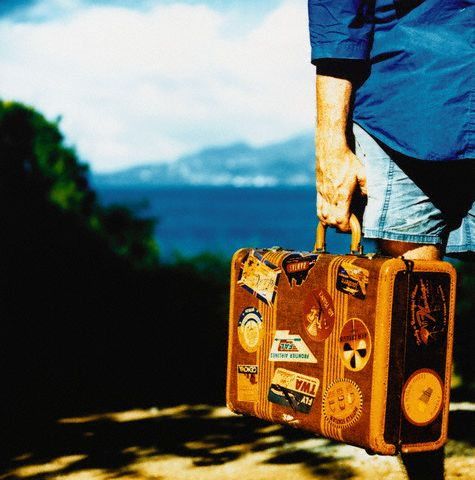 Hand Holding Suitcase Covered with Labels